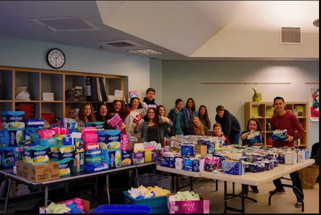 High School students behind tables covered with donated supplies for the Homeless Period Project