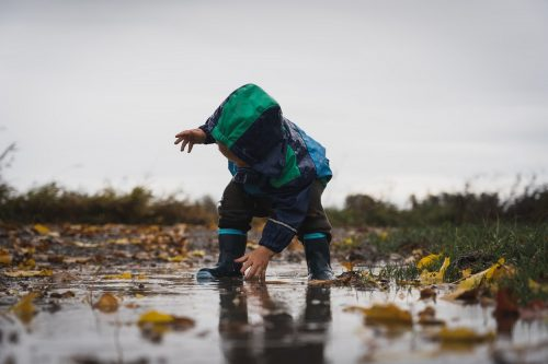 Child in Raingear is Playing in a Puddle