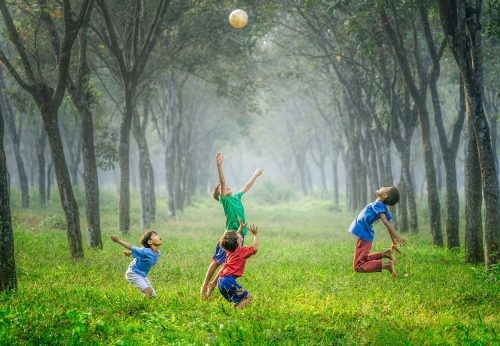 Barefooted boys leap for joy while playing volleyball in the forest